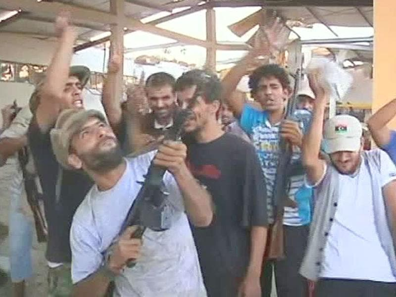 Libyan rebels celebrate in a town where the rebel took the base of the elite 32nd Brigade commanded by Muammar Gaddafi's son, Khamis, 16 miles west of Tripoli, Libya.