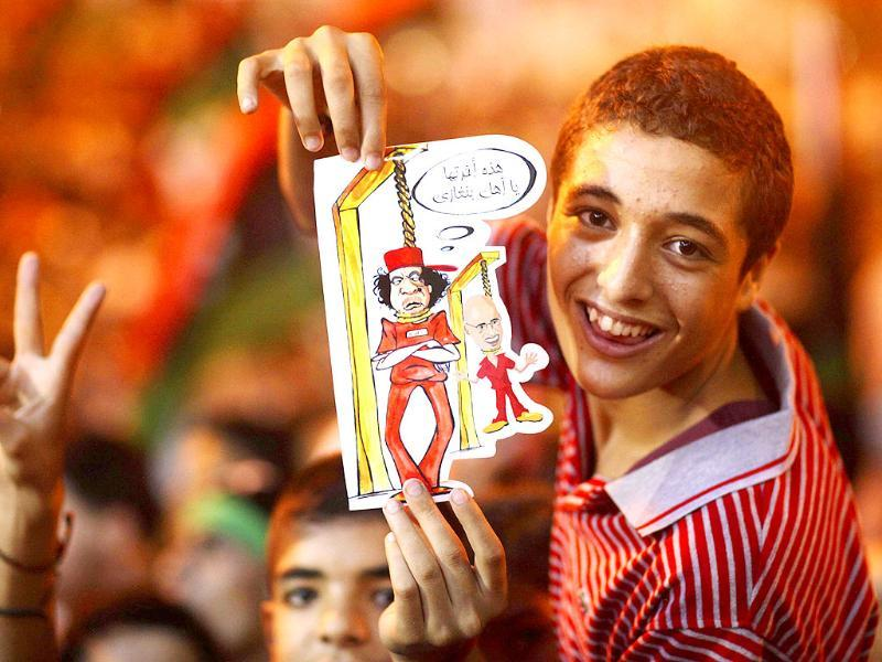 A boy holds a drawing depicting Muammar Gaddafi and his son Seif al-Islam being hanged during celebrations of the capture in Tripoli of the son at the rebel-held town of Benghazi, Libya.