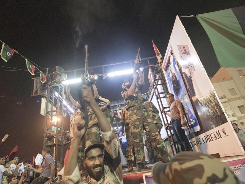 A Libyan rebels security forces member fire their rifles in the air as tens of thousands of libyans celebrate the news of the arrest of Gaddafi's son Saif al-islam and the partial fall of Tripoli in the hands of the Libyan rebels in Benghazi, Libya.