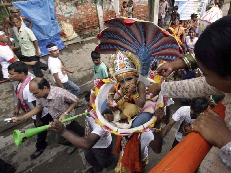 A man carries a child dressed as Lord Krishna on his head as devotees take to a street for parading as part of Janmashtami celebrations in Dhaka, Bangladesh.