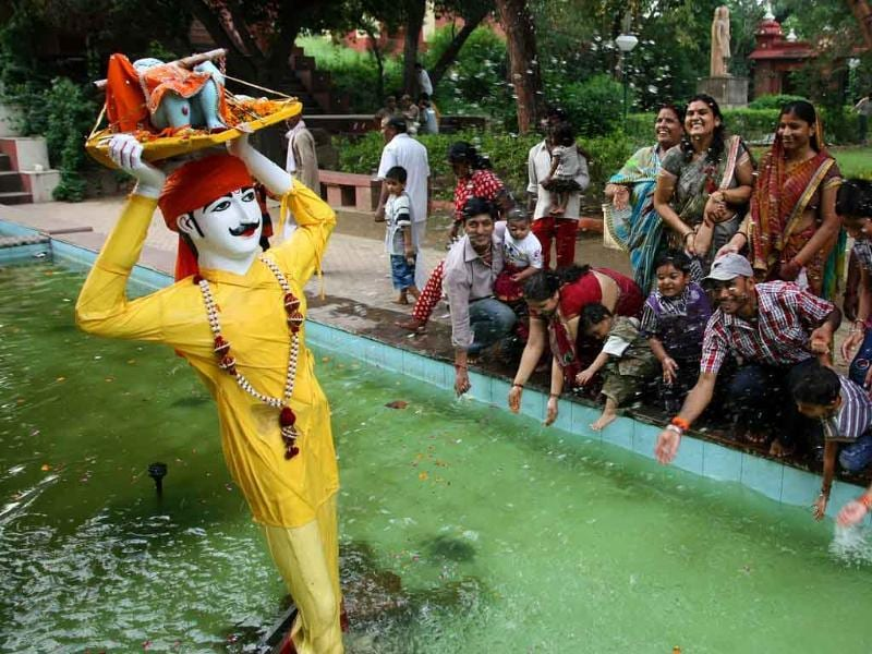 The devotees splash water on the tableau of Lord Krishna at Birla Mandir on the occasion of Janmashtmi festival.
