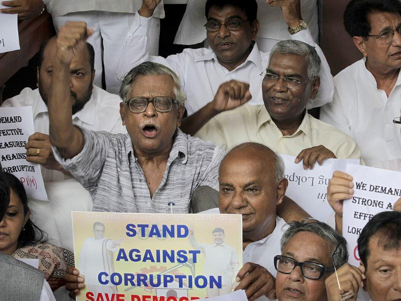 Leaders hold placards during a protest against corruption and demanding strong anti-corruption legislation in front of the parliament.