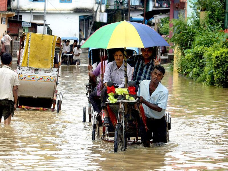 A rickshaw puller wades through a waterlogged street after heavy rains in Dimapur, Nagaland.