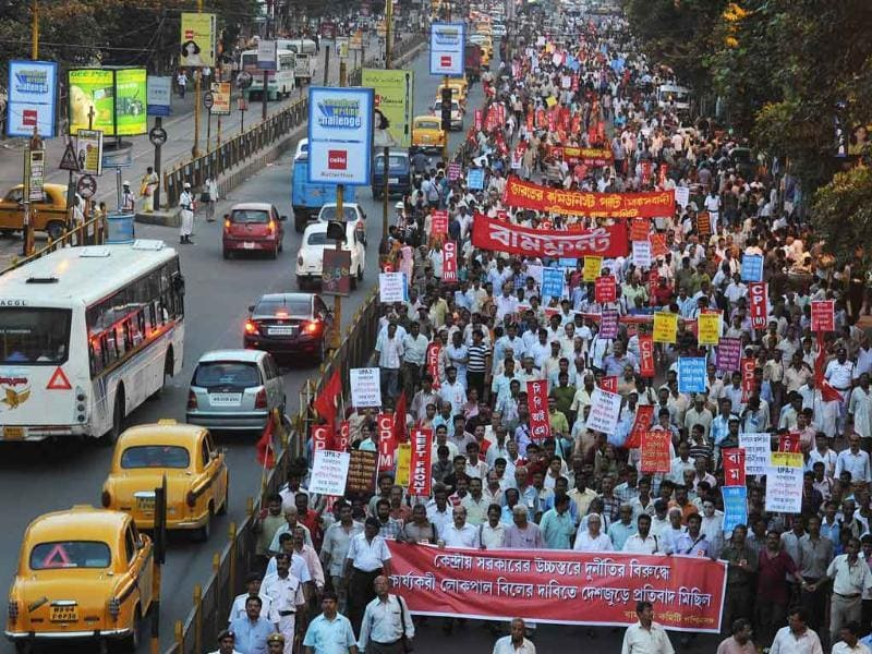 Leftist activists carry party flags and placards as they participate in a mass rally protesting against the Govt and supporting Anna Hazare.