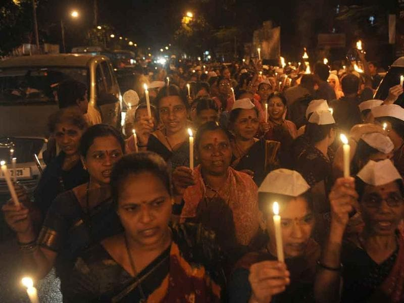 Wives of policemen hold candles and torches as they walk during a march in support of social activist Anna Hazare in Mumbai.