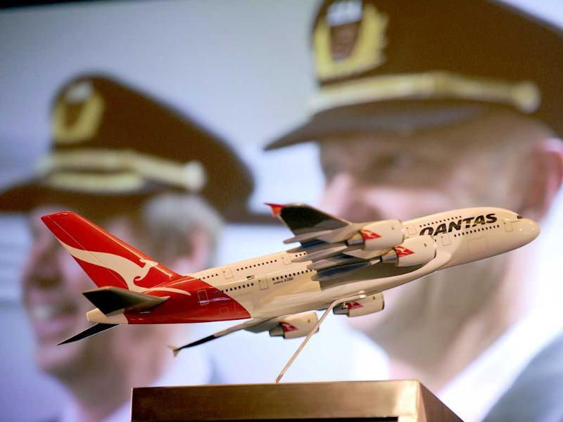 A model Qantas aeroplane sits on the stage as a photo of a Qantas employee is projected onto a screen during the release of company full-year results in Sydney.