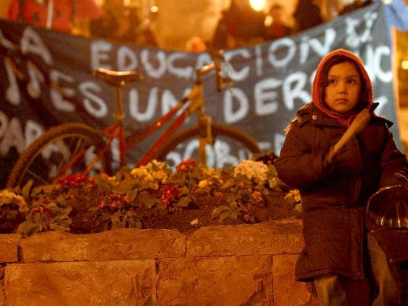 A child beats cooking utensils in front of a banner that reads The education is a right during a rally to demand changes in the public state education system, at Santiago.