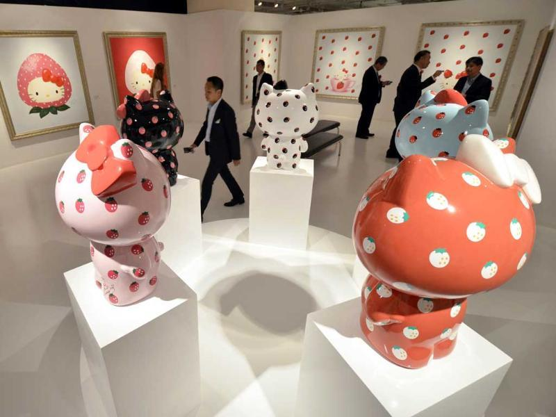 Vistors look at paintings and statues of Hello Kitty, designed by Hello Kitty creator Yuko Yamaguchi at a preview of a Hello Kitty Art Exhibition in Tokyo.