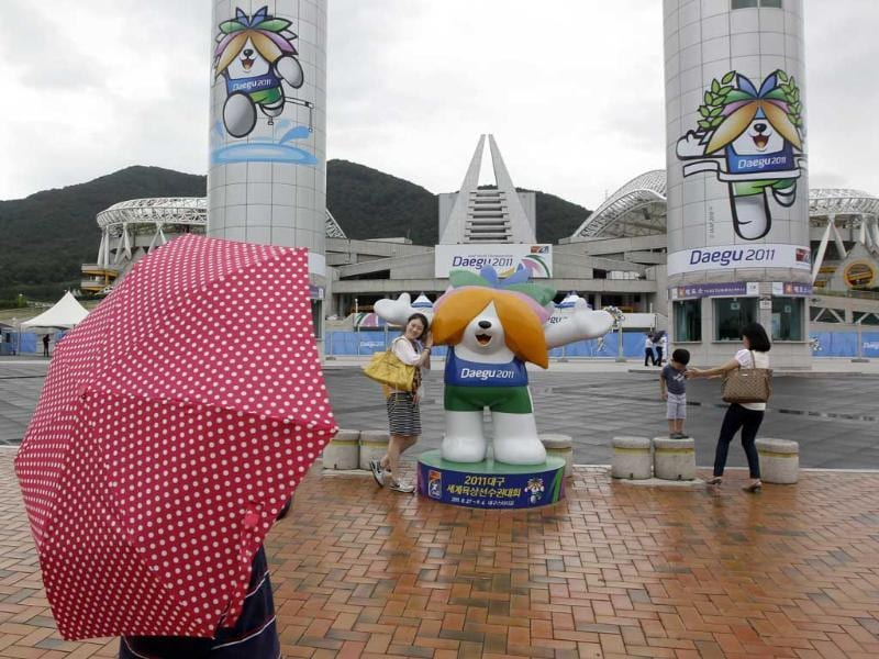 A woman poses close with the mascot of World Athletics Championships outside the stadium in Daegu, South Korea.