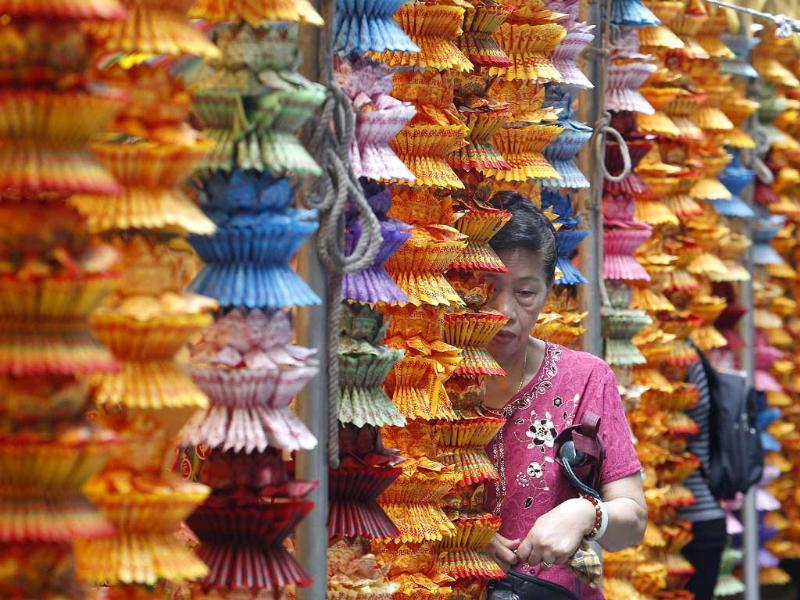 A person walks between strings of lotus-shaped incense papers during a mass prayer for the Chinese Hungry Ghost Festival in Taipei.