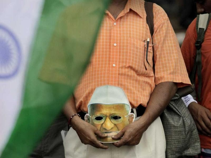 A supporter of anti-corruption activist Anna Hazare holds his mask, on the ninth day of Hazare's hunger strike in New Delhi.