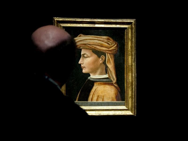 Visitors look at Italian painter Domenico Veneziano's painting Portait of a Man (L) during a press preview of the exhibition Renaissance Faces - Masterpieces of Italian Portraiture at Berlin's Bode Museum.