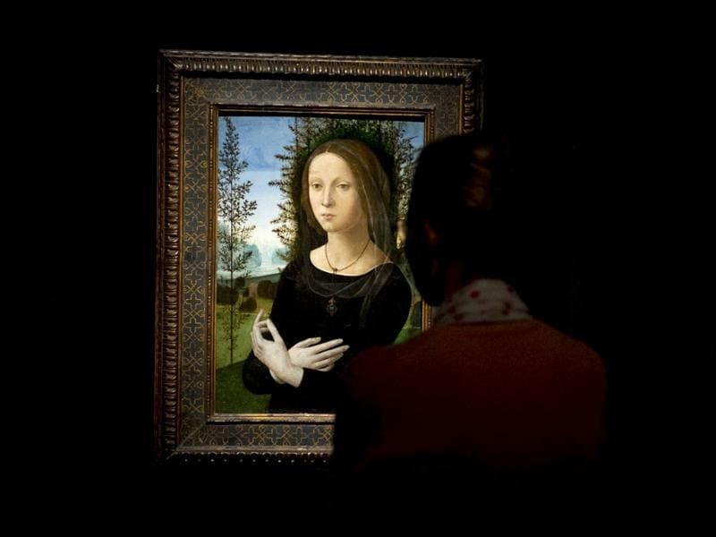 A visitor looks at Italian painter Lorenzo di Credi's Portrait of a Young Woman during a press preview of the exhibition Renaissance Faces - Masterpieces of Italian Portraiture at Berlin's Bode Museum.