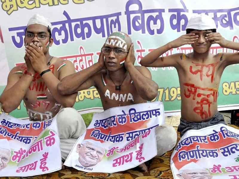 Anna Hazare supporters pose as Gandhiji's three monkeys during a protest in Moradabad.