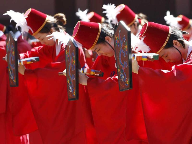 College students wearing traditional Korean costumes dance during a graduation ceremony at Sungkyunkwan University in Seoul. The students took part in the traditional performance for their senior graduates.