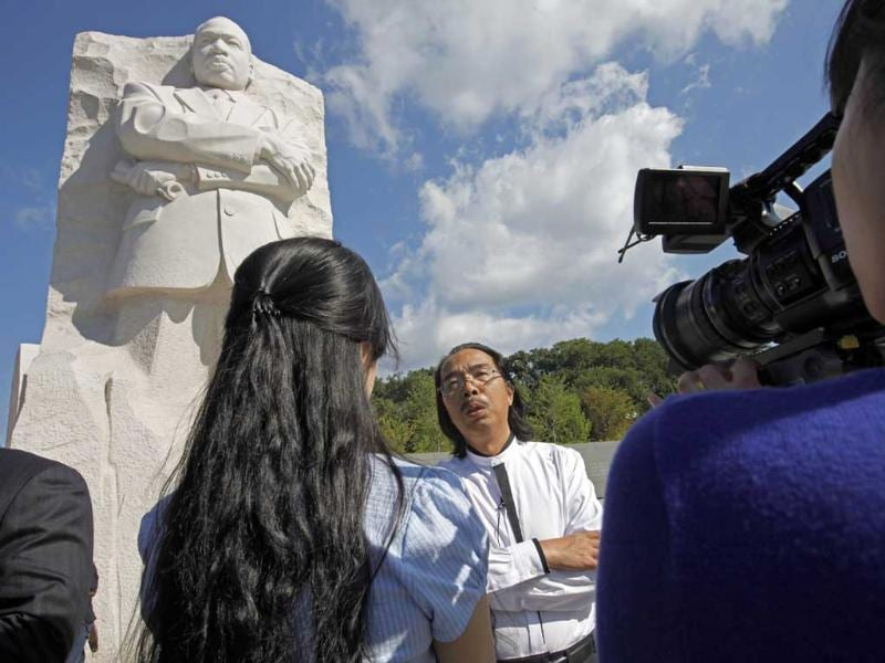 Sculptor Lei Yixin, of China, is interviewed by a Chinese television crew in front of his sculpture of Dr. Martin Luther King, Jr.