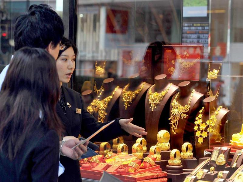 A sales woman walks to protective customers outside a jewelry store in Hong Kong. Gold stood at 1,759.32 USD per ounce on the spot market.