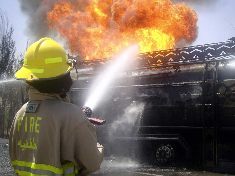 An Afghan fire fighter tries to extinguish a burning fuel tanker carrying fuel supplies for NATO in Logar, Afghanistan.