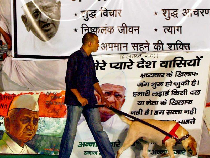 A security person inspects with a sniffer dog near Anna Hazare's stage at Ramlila Ground.