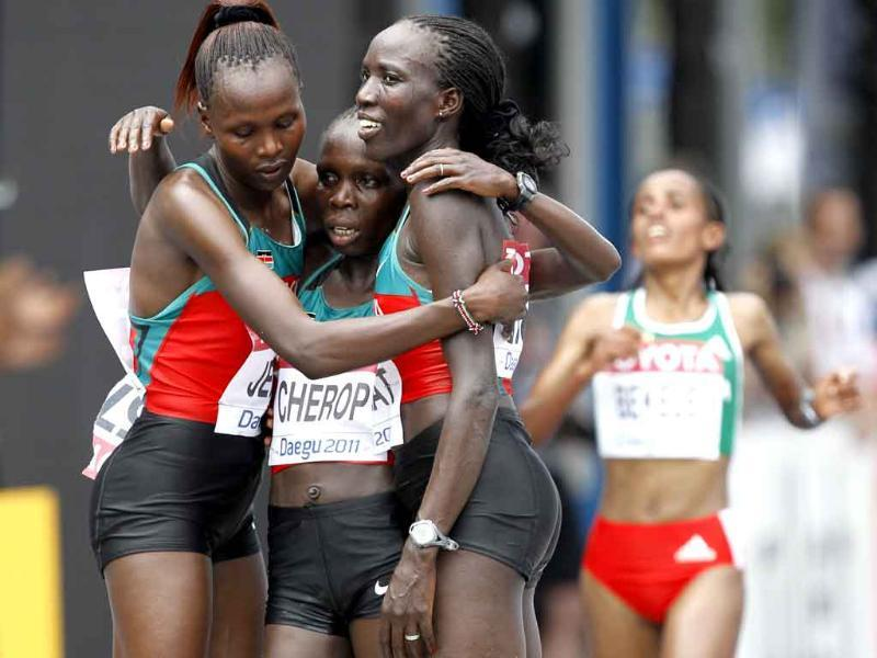 Kenya's gold medalist Edna Ngeringwony Kiplagat, right, embraces teammates and silver medalist Priscah Jeptoo, left, and bronze medalist Sharon Jemutai Cherop following the Women's Marathon at the World Track and Field Championships in Daegu, South Korea.