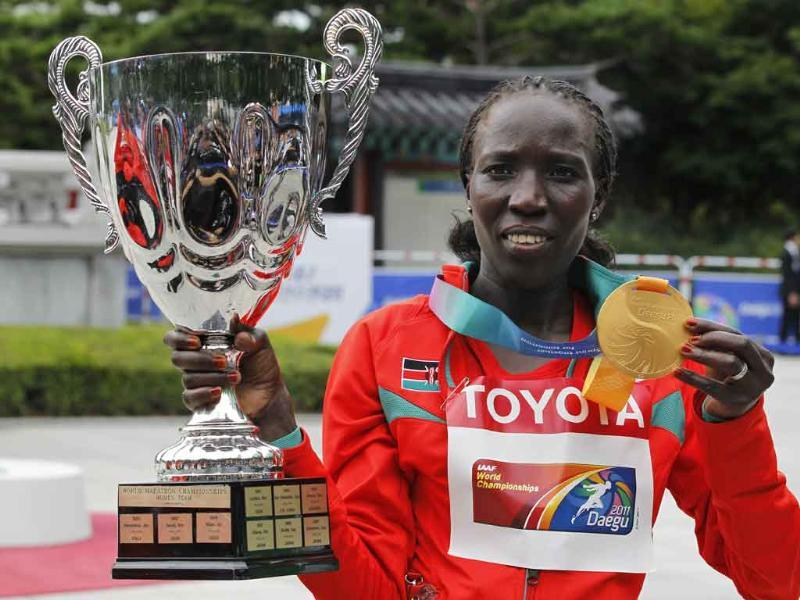 Kenya's Edna Ngeringwony Kiplagat poses with her gold medal and trophy for the Women's Marathon at the World Athletics Championships in Daegu, South Korea.