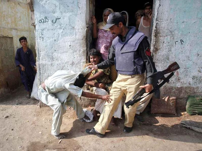 A policeman grabs a man as he protests while being detained during a search operation in Karachi. A search operation started by law enforcement agencies against criminals entered its third day as a dozen more suspects were taken into custody from different areas of Karachi.