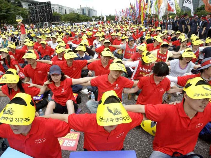 South Korean workers form a scrum during a rally against the government's labor policy near the National Assembly in Seoul, South Korea. About 10,000 Korean Financial Industry Union and Public Union members demanded wage hikes and better working conditions.