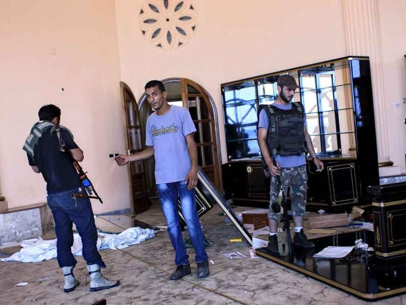 Rebel fighters walk inside the house of Al-Saadi Gaddafi, the son of Libyan dictator Muammar Gaddafi in Tripoli, Libya. A defiant Muammar Gaddafi vowed to fight on
