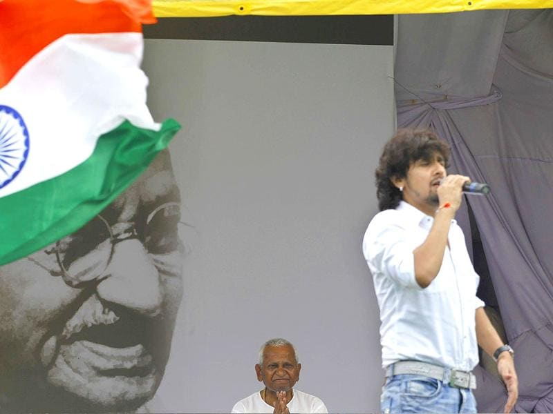 Anna Hazare listens to devotional and nationalist songs being sung by a popular bollywood singer Sonu Nigam, right, in New Delhi, Saturday.