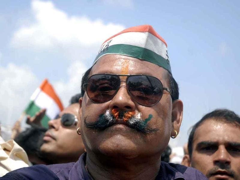 A man paints his moustache with tri-colours as veteran social activist Anna Hazare breaks his fast, after government caved in to his demands at Ram Lila Maidan.