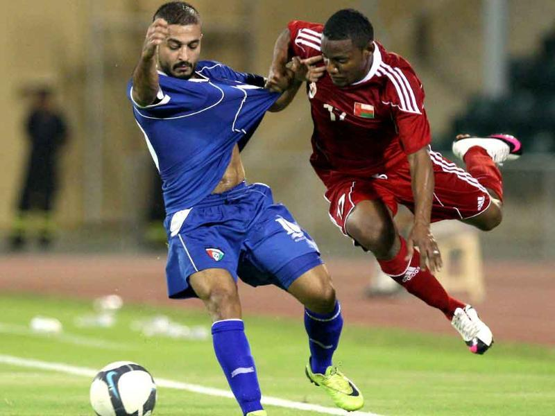 Oman's Hassan al-Ghailani (R) challenges Kuwait's Abdel Aziz Meshan during their friendly football match in Muscat.