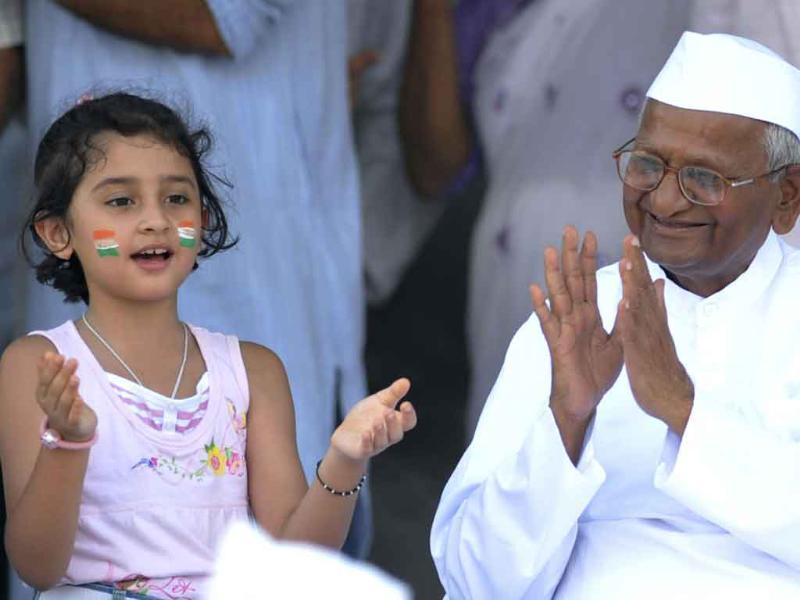 Anti-corruption activist Anna Hazare shares a light moment with a child on stage before breaking his fast on the 13th day of his hunger strike at the Ram Lila grounds in New Delhi.