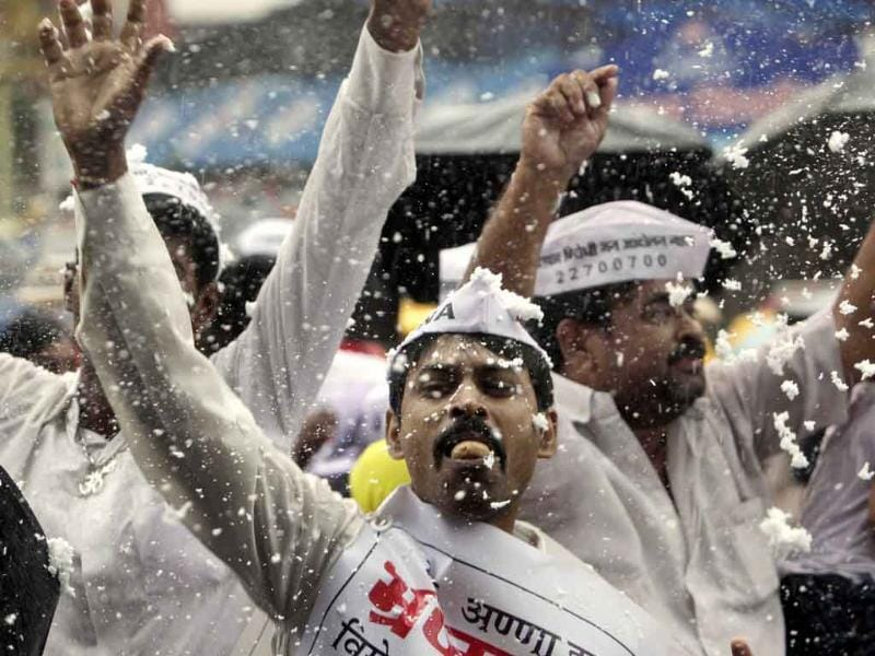 A man bites a piece of sweet and dances in jubilation as supporters of activist Anna Hazare spray foam and celebrate in Mumbai. Hazare, whose protest galvanized the nation's anger against corruption ended his 13-day hunger strike after forcing the Parliament to throw its weight behind his crusade
