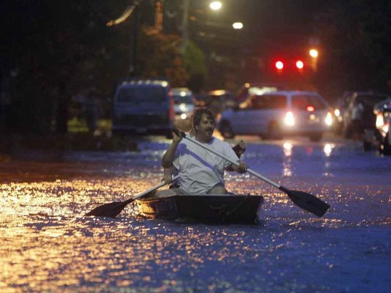 Two men paddle a boat in a street flooded by Hurricane Irene as it approaches Monteo, NC.