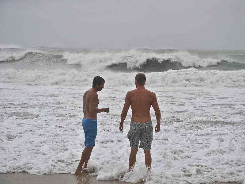 Two men enjoy the rough surf at the beach in Nags Head in the Outer Banks of North Carolina as Hurricane Irene pounded the coast of North Carolina.