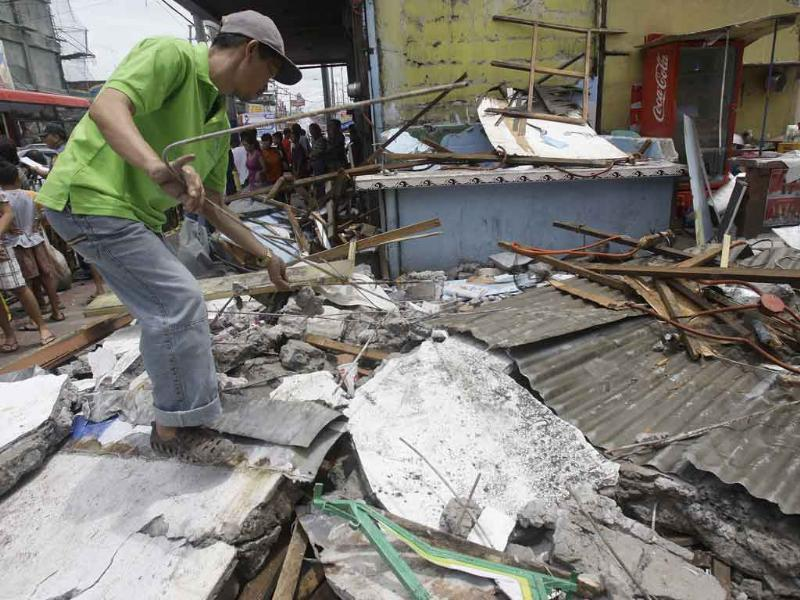A man salvages steel rods on the rubble of a collapsed wall as it was knocked down by strong winds, in suburban Novaliches, Quezon City, Philippines.