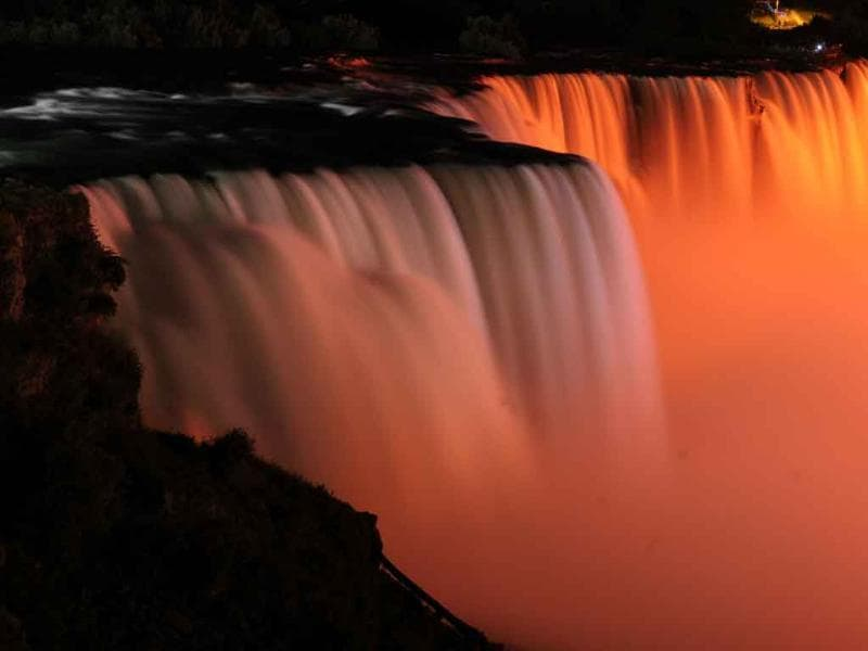 Niagara Falls is illuminated in orange, to honor the late New Democrats party leader Jack Layton in Niagara Falls, New York.