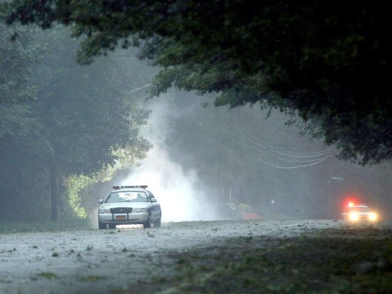 A police car drives past a fire that was ignited by a fallen live electric wire on Old Bethpage Road in Old Bethpage, New York.