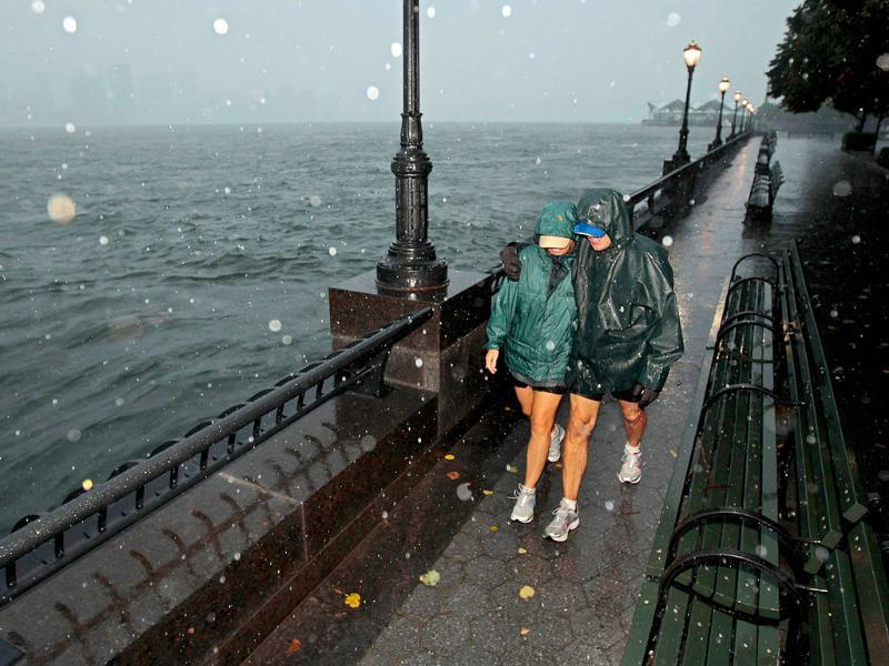 SoHo residents Amy Eagle (L) and Rich Thompson take an early morning walk just before high tide along the World Financial Center Esplanade as the effects of Hurricane Irene are felt in Manhattan in New York City.
