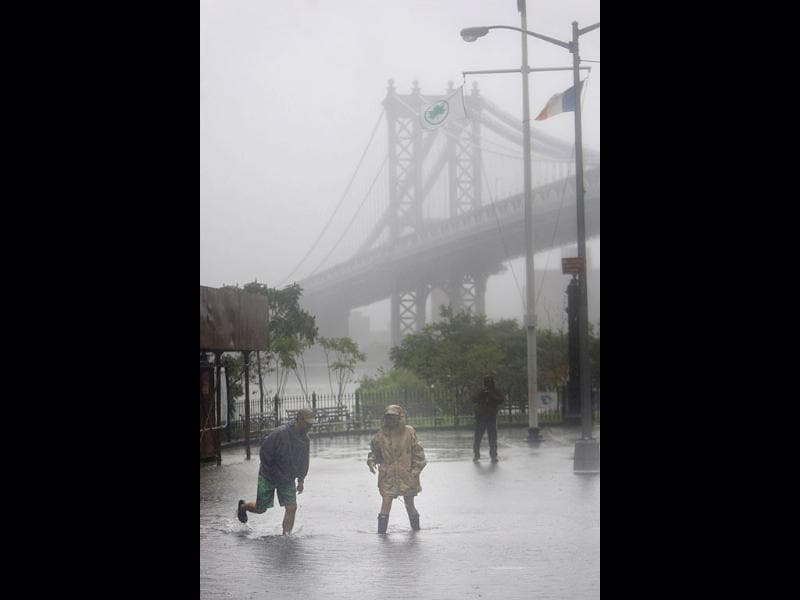Eddie Lima, left, and Nancy Zakhary wade through a flooded area near the Brooklyn Bridge in New York.