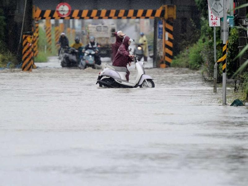 Local motorcyclists push their motorbikes through floodwaters caused by Typhoon Nanmadol in Linbian, Taiwan's southern Pingtung county.
