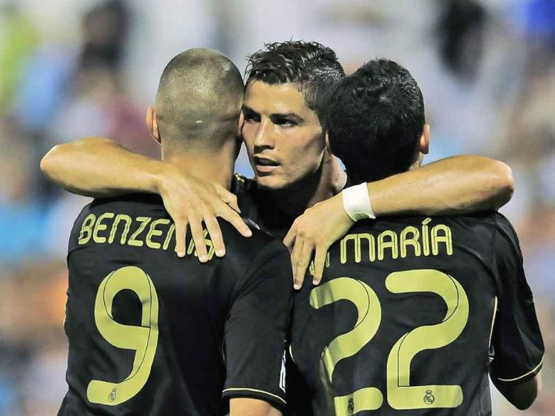 Real Madrid's Cristiano Ronaldo, center, celebrates his second goal between his fellow teammate Karim Benzema from France, left, and Angel Di Maria from Argentina, after scoring against Real Zaragoza during their Spanish La Liga soccer match at La Romadera stadium in Zaragoza, Spain.
