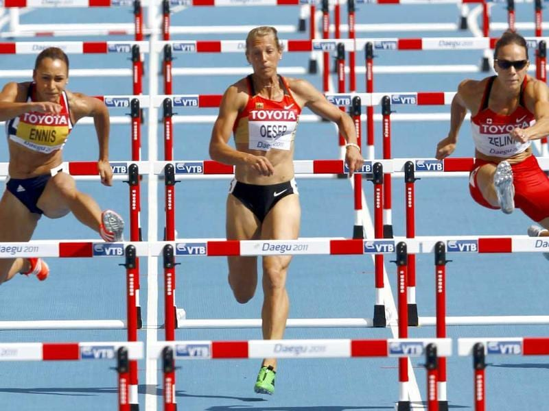 Jessica Ennis of Britain (L) and Jessica Zelinka of Canada (R) clear a hurdle next to Jennifer Oeser of Germany during their 100 metres hurdles heat of the heptathlon at the IAAF World Championships in Daegu.