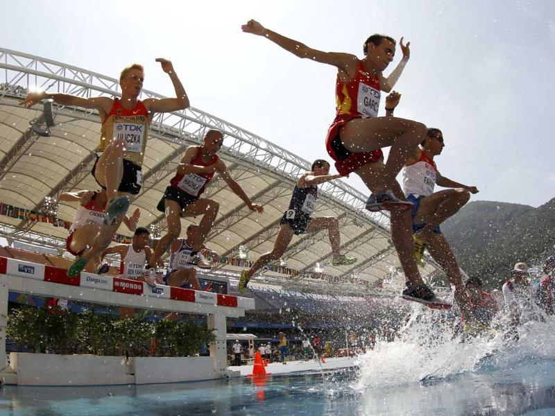 Competitors clear a water jump during the men's 3,000 metres steeplechase heat at the IAAF World Championships in Daegu.
