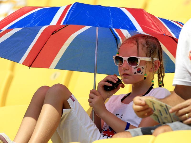 A spectator uses an umbrella to shade herself from the sun at the World Athletics Championships in Daegu.