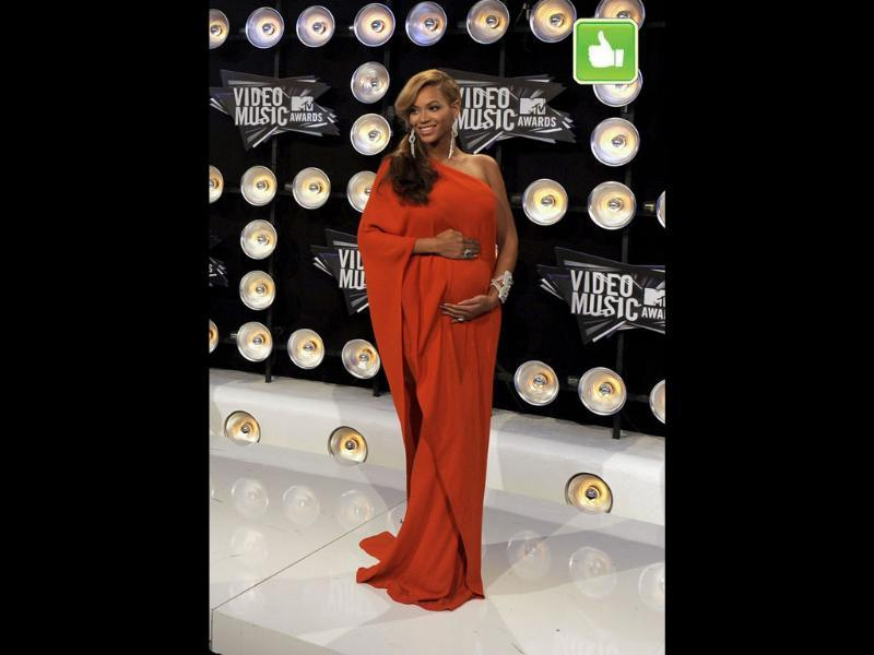 With her flowy orange dress, minimal jewelry and classic golden hair, Beyonce makes being pregnant looks so easy and so sexy!
