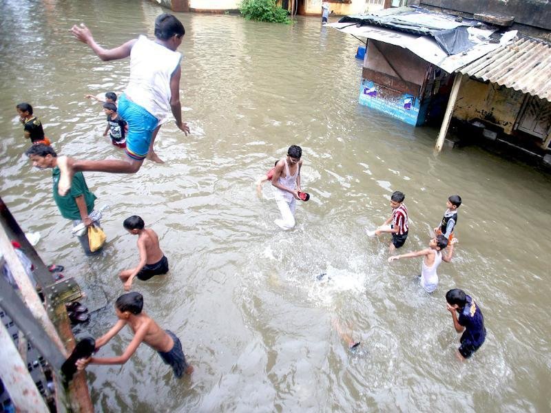 Boys play in flooded water at BPT colony in Wadala after heavy rain in Mumbai.