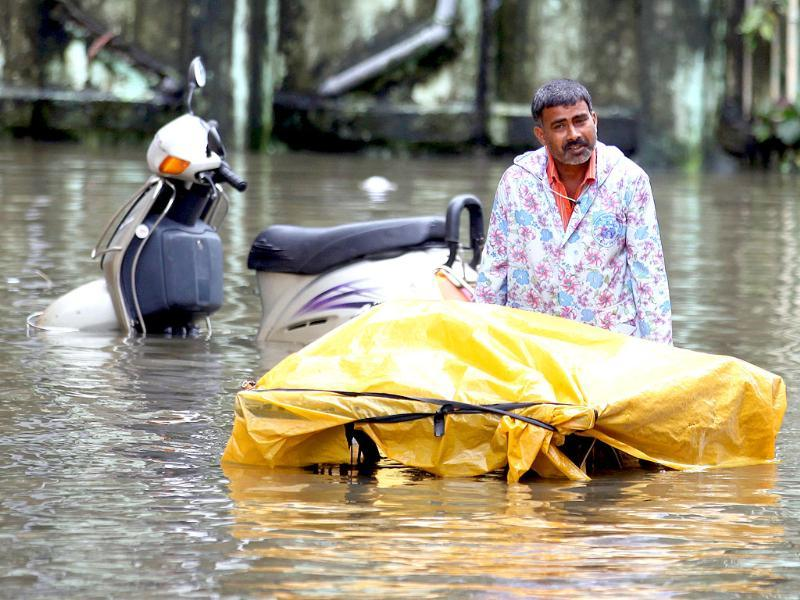 Vegetable vendor walks through flooded water in BPT colony at Wadala during heavy rain in Mumbai.