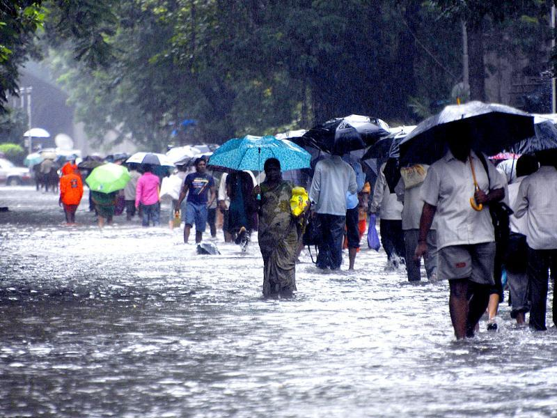 People walk through a waterlogged road at Dadar after heavy rains in Mumbai.