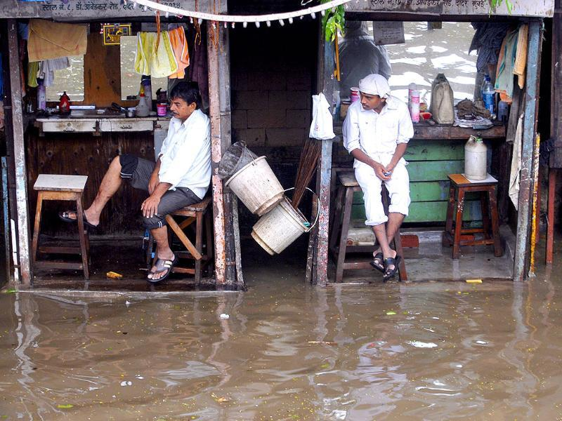 Locals look on helplessly as rain water enters their shops at Hindmata, Parel after heavy rains in Mumbai.